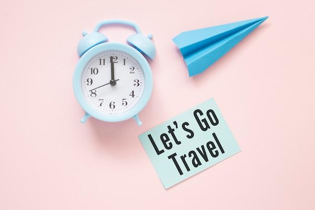 Let's go travel testo su carta con orologio e aeroplano di carta su un tavolo rosa.