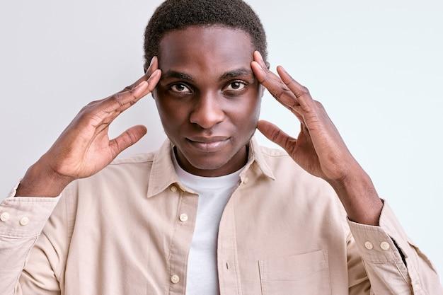 Fammi pensare. fiducioso uomo africano nero toccando templi, stare con pensieri profondi