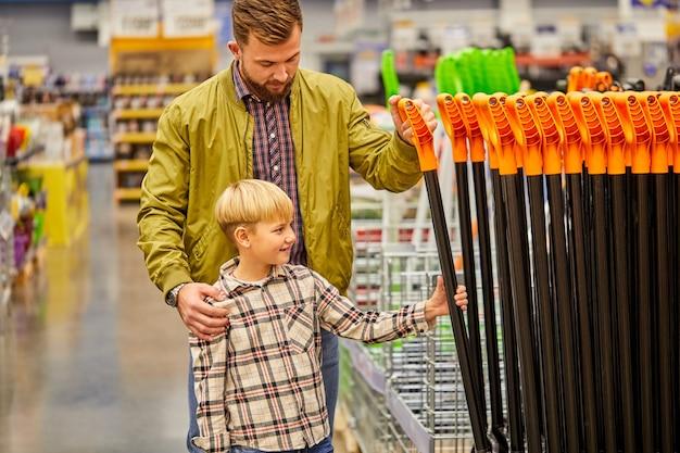 Prendiamo questo. ragazzo e uomo che comprano la pala in negozio, fanno la scelta e discutono insieme. nella navata