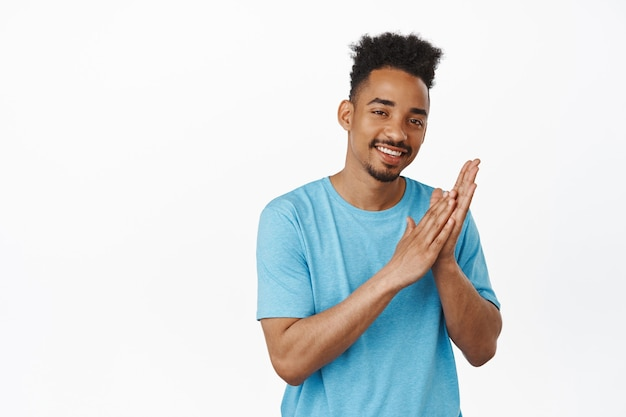 Andiamo al sodo. sorridente determinato ragazzo afroamericano si strofina le mani compiaciuto, assapora la grande opportunità, pronto a fare qualcosa, in piedi sul bianco