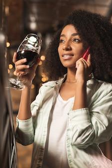 Incontriamoci. splendida donna riccia parla al telefono e invita la sua amica a bere qualcosa insieme mentre beve vino al bar