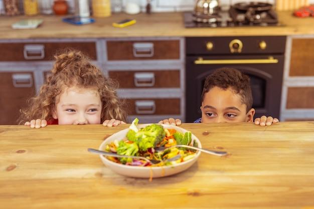 Giochiamo. felice ragazzo brunetta appoggiato al tavolo mentre si diverte con suo cugino