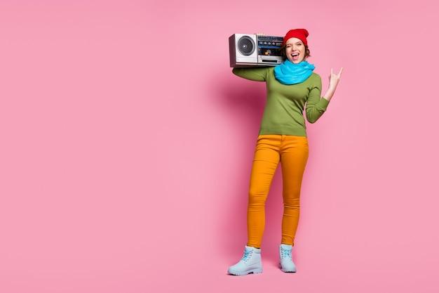 Rockeggiamo! foto a figura intera ragazza pazza tenere retrò boom box fare segno di corna strizzatina d'occhio lampeggiare godere di pank weekend indossare verde blu rosso copricapo ponticello pantaloni scarpe bianche isolato muro di colore rosa