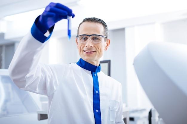 Vediamo. joyfull ha determinato il ricercatore maschio che fa oscillare la provetta con liquido blu mentre la esaminava e si trovava in laboratorio