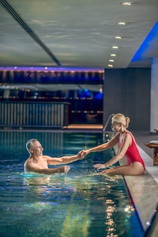 Nuotiamo. carina donna bionda in costume da bagno rosso che dà la mano a suo marito nella piscina di na