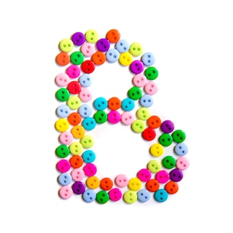 Lettera b dell'alfabeto inglese da un gruppo di piccoli pulsanti colorati su fondo bianco