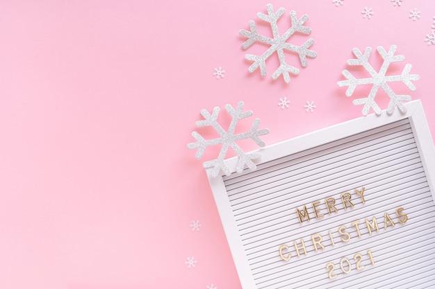 Bordo delle lettere con auguri di buon natale, fiocco di neve decorativo su sfondo girly rosa pastello