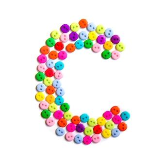 Lettera c dell'alfabeto inglese da un gruppo di piccoli pulsanti colorati su bianco