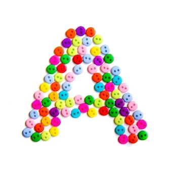 Lettera a dell'alfabeto inglese da un gruppo di piccoli pulsanti colorati su fondo bianco