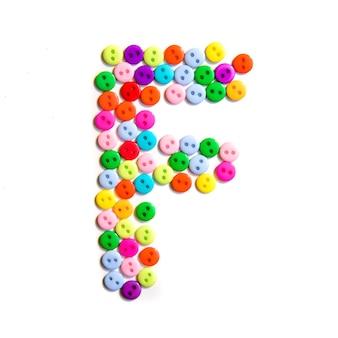 Lettera f dell'alfabeto inglese da un gruppo di piccoli pulsanti colorati su bianco