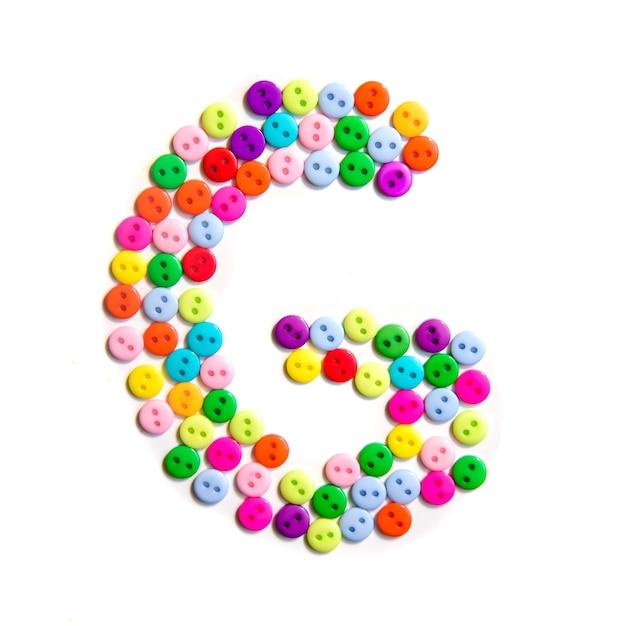 Lettera g dell'alfabeto inglese da un gruppo di piccoli pulsanti colorati su bianco