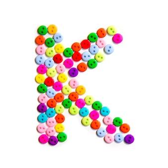 Lettera k dell'alfabeto inglese da un gruppo di piccoli pulsanti colorati su fondo bianco