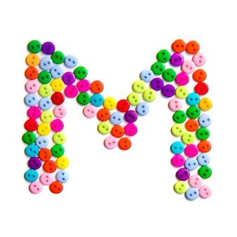 Lettera m dell'alfabeto inglese da un gruppo di piccoli pulsanti colorati su fondo bianco