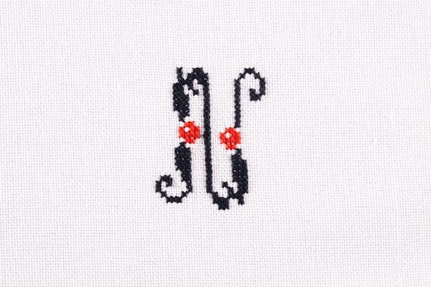 Lettera n di tessuto di lino alfabeto latino ricamato a punto croce fatto a mano