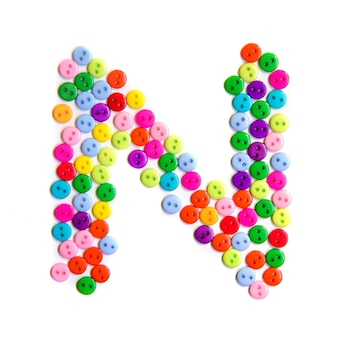Lettera n dell'alfabeto inglese da un gruppo di piccoli pulsanti colorati su fondo bianco