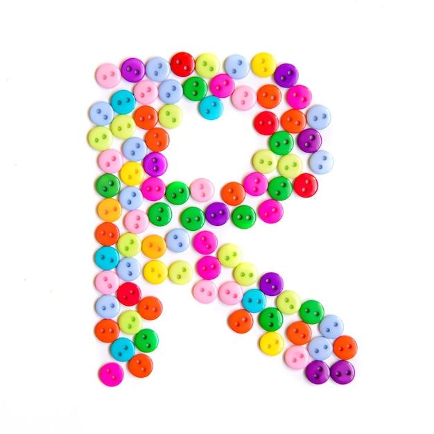 Lettera r dell'alfabeto inglese da un gruppo di piccoli pulsanti colorati su bianco