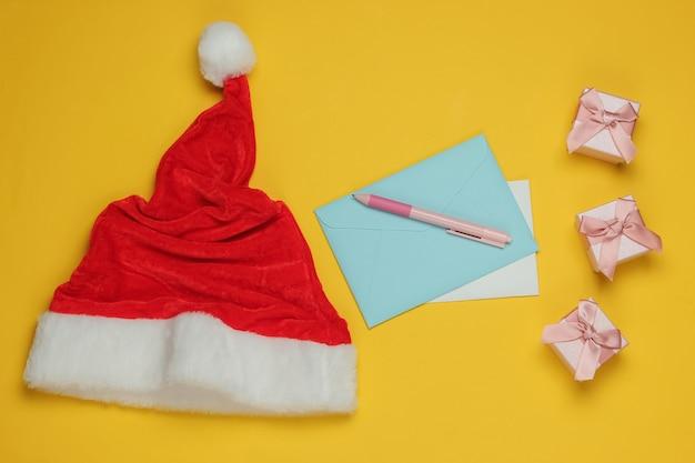 Lettera a babbo natale. cappello da babbo natale, busta con lettera e penna, scatole di regali su sfondo giallo. natale laici piatta. vista dall'alto