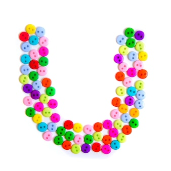 Lettera u dell'alfabeto inglese da un gruppo di piccoli pulsanti colorati su bianco
