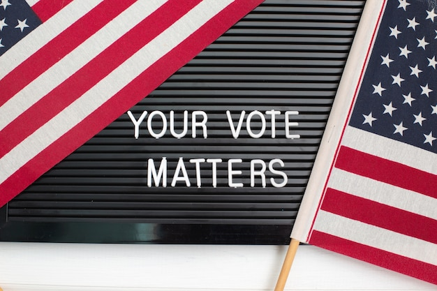 Segno della lavagna con le parole il tuo voto è importante con la bandiera americana. elezioni americane.