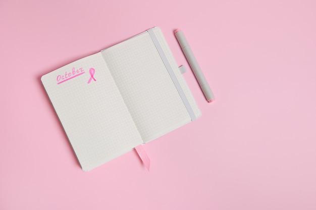 Iscrizione 1 ottobre su un diario e un nastro rosa su un foglio di carta bianco vuoto, isolato su sfondo rosa con spazio di copia. giornata mondiale contro il cancro al seno