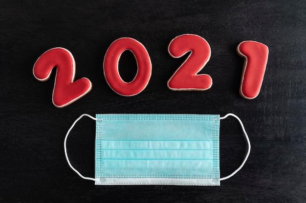 Lettering 2021 e mascherina medica su sfondo nero. estensione della quarantena covid nel 2021.