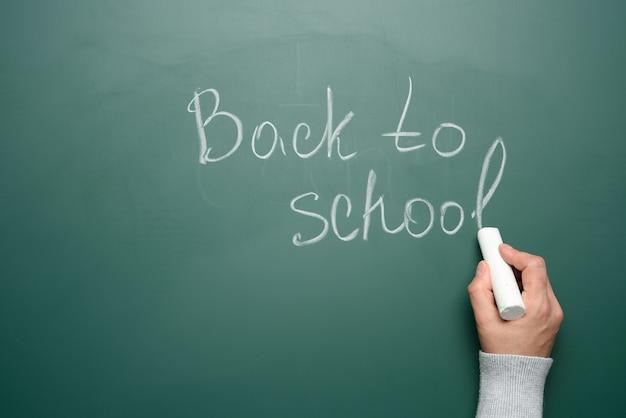 Lettering torna a scuola in gesso bianco su una lavagna verde, concetto di inizio anno scolastico