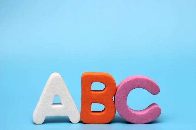 Le lettere abc sono isolate su uno sfondo blu. imparare una lingua straniera.