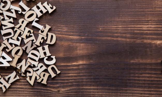 Lettere dell'alfabeto inglese su uno sfondo di legno scuro. il concetto di educazione, giochi di parole, cucito. spazio per il testo
