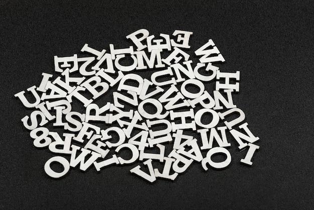 Lettere dell'alfabeto latino disposte in ordine caotico. sfondo nero.