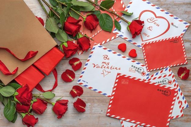Lettere con francobolli stelle strisce cerchi cuori regali rose e petali su fondo in legno