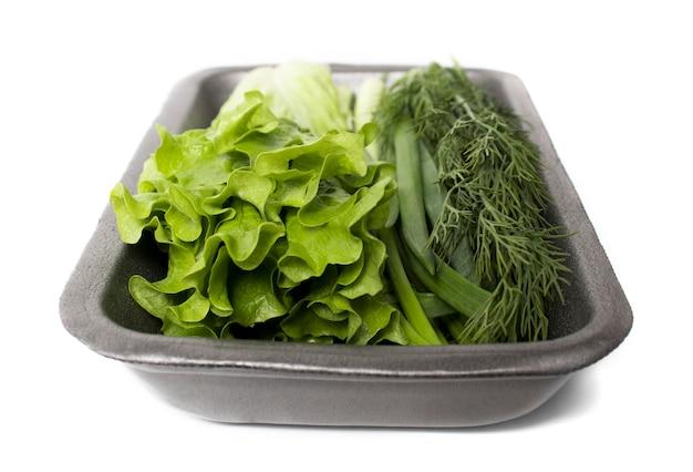 Lattuga, aneto e cipolle verdi in un contenitore su uno sfondo bianco. verdure fresche. cibo zod ecologico, una corretta alimentazione