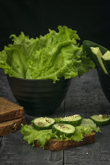 Foglie di lattuga, cetrioli e pane su un tavolo di legno