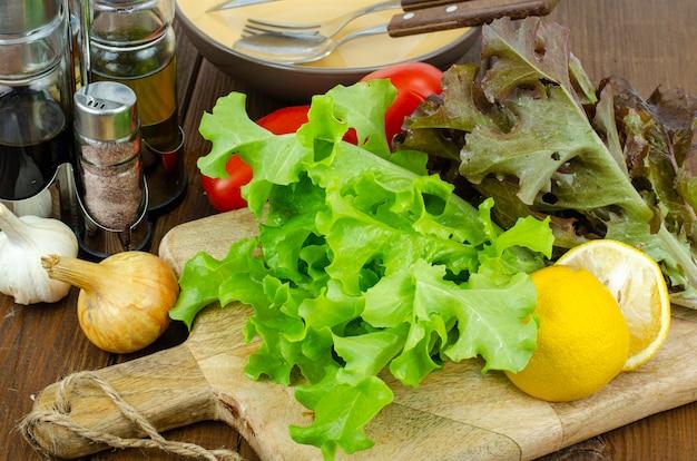 Foglie di lattuga su tagliere di legno, set di spezie per cucinare. foto dello studio.