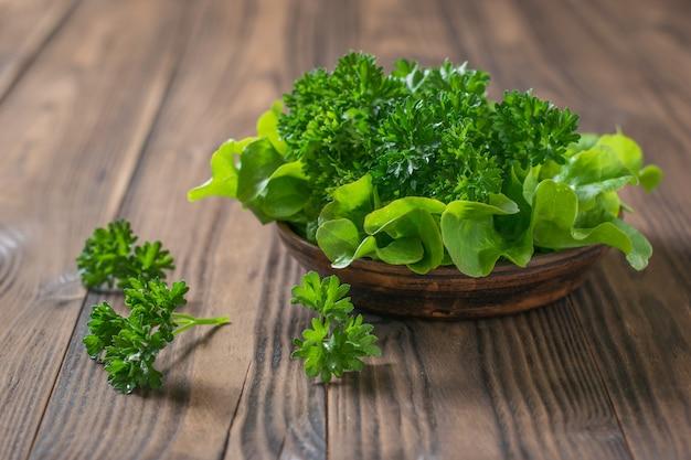 Lattuga e prezzemolo in una ciotola di argilla su un tavolo di legno con una forchetta. il concetto di mangiare sano.