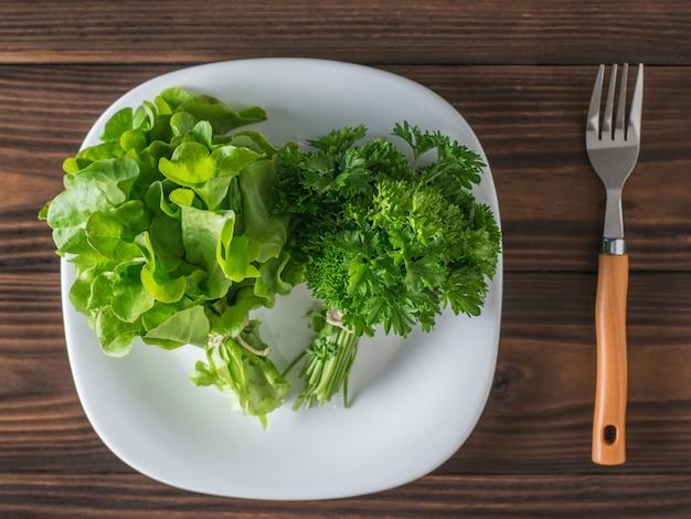 Lattuga e prezzemolo in una ciotola bianca su un tavolo di legno con una forchetta. il concetto di mangiare sano. lay piatto.
