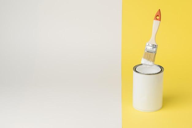 Pennello levitante su una lattina di vernice su uno sfondo giallo e bianco. esecuzione di lavori di pittura. posto per il testo.