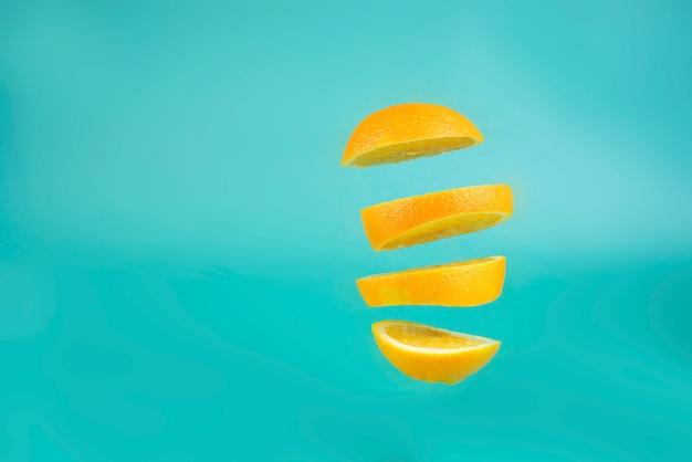 Levitazione arancione tagliato arancione su sfondo blu