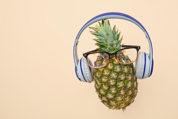 Ananas levitante con occhiali e cuffie su uno sfondo giallo chiaro con spazio per le copie