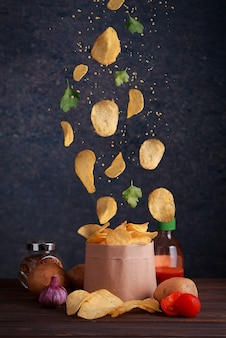 Patatine fritte levitanti. le patatine cadono in un sacchetto artigianale con patate, pomodori sul tavolo di legno