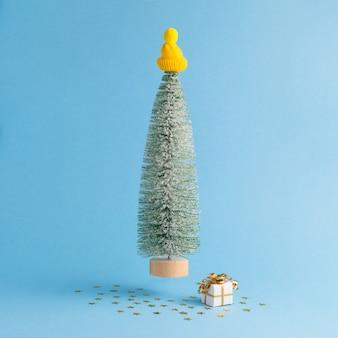 Levitazione dell'albero di natale e del regalo su sfondo blu pastello