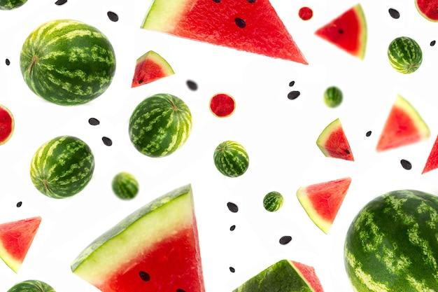 Levitazione di cocomero pezzi maturi di anguria in sfondo bianco frutti nell'aria che volano rosso f...