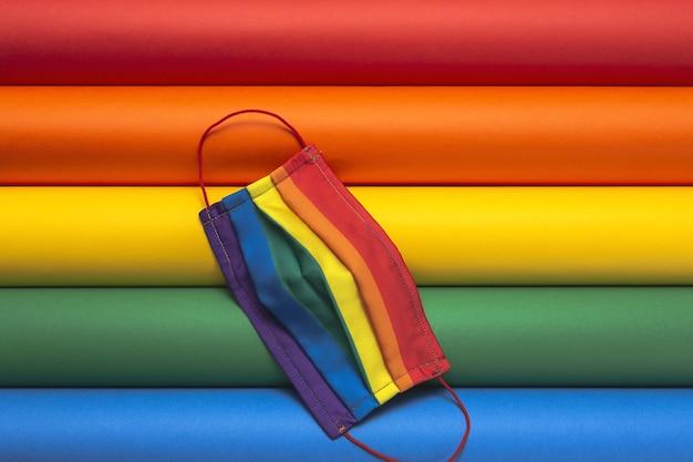 Sfondo lgbt con maschera protettiva color arcobaleno dall'alto. lay piatto. virus covid-19