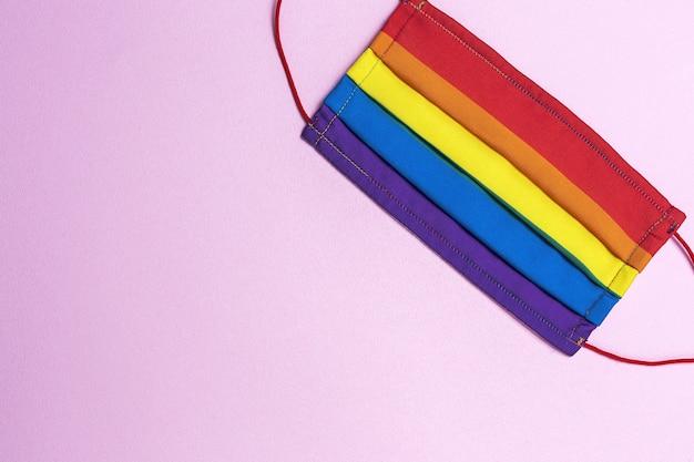 Sfondo lgbt con maschera protettiva color arcobaleno dall'alto. disposizione piatta. virus covid-19