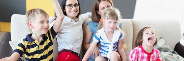 Famiglia lgbt due donne con bambini gioiosi tengono la bandiera