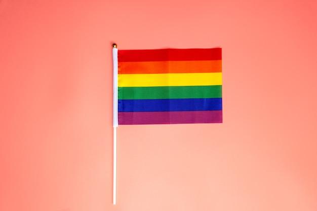 Bandiera arcobaleno lgbt, bandiera dell'orgoglio sulla superficie rosa, vista dall'alto con lo spazio della copia