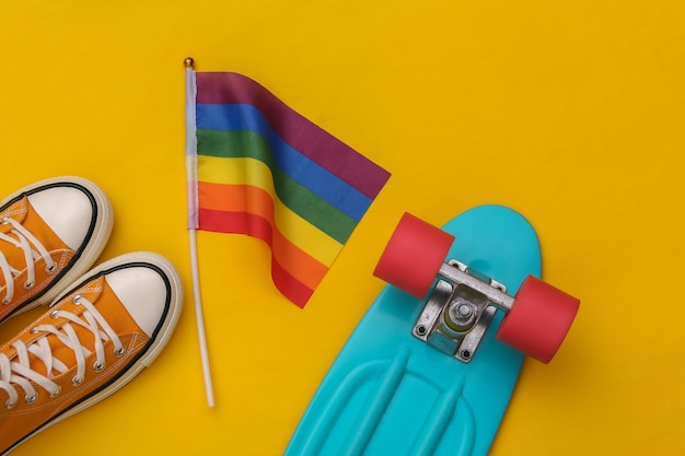 Bandiera arcobaleno lgbt e scarpe da ginnastica, bordo dell'incrociatore su sfondo giallo. tolleranza, libertà, parata gay