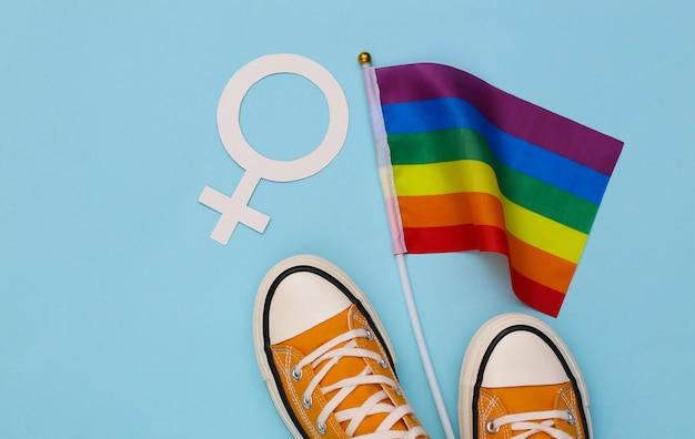 Bandiera arcobaleno lgbt e scarpe da ginnastica, simbolo femminile su sfondo blu. tolleranza, libertà, parata gay. vista dall'alto