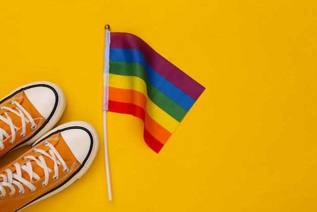 Bandiera arcobaleno lgbt e scarpe da ginnastica su sfondo giallo. tolleranza, libertà, parata gay