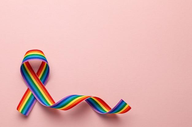 Simbolo del nastro dell'orgoglio del nastro arcobaleno lgbt. stop all'omofobia. sfondo rosa. copia spazio per il testo.