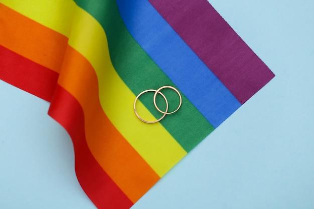 Matrimonio lgbt. bandiera arcobaleno lgbt e anelli d'oro su sfondo blu. tolleranza, libertà